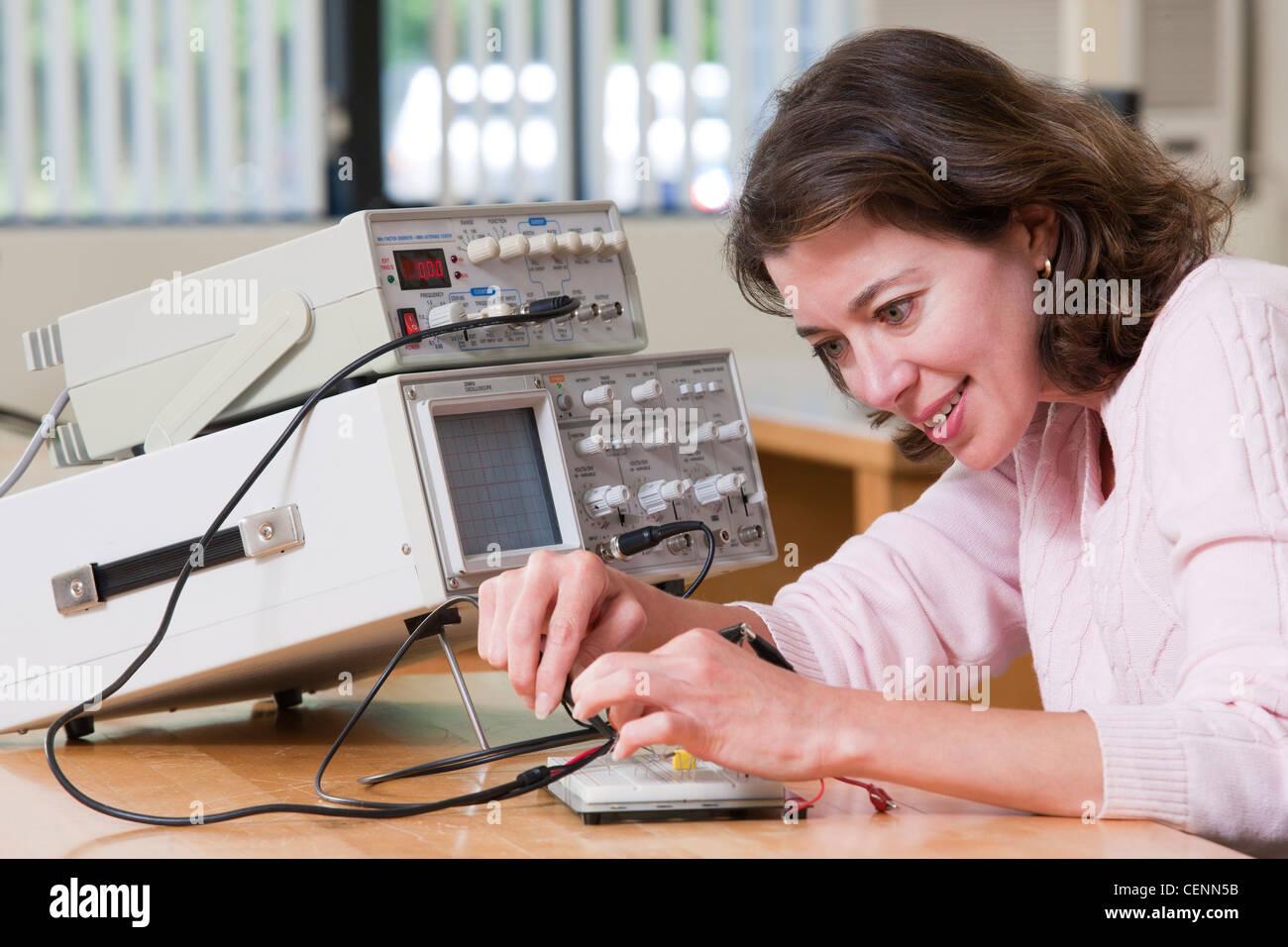Élève ingénieur dans l'établissement des connexions sur le circuit de test pour l'expérience Photo Stock