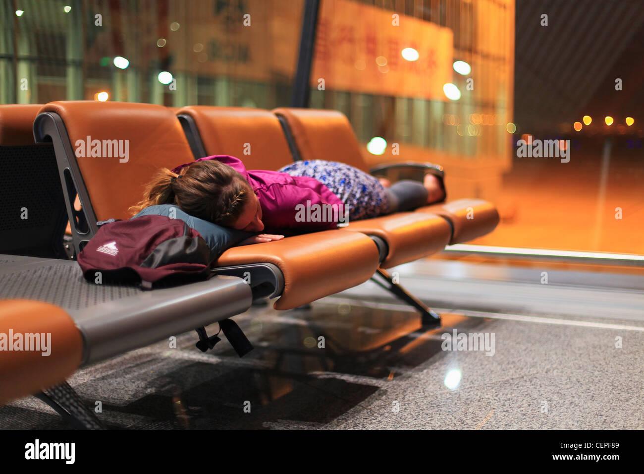 Une fille dormir sur des chaises dans un aéroport; Beijing, Chine Photo Stock