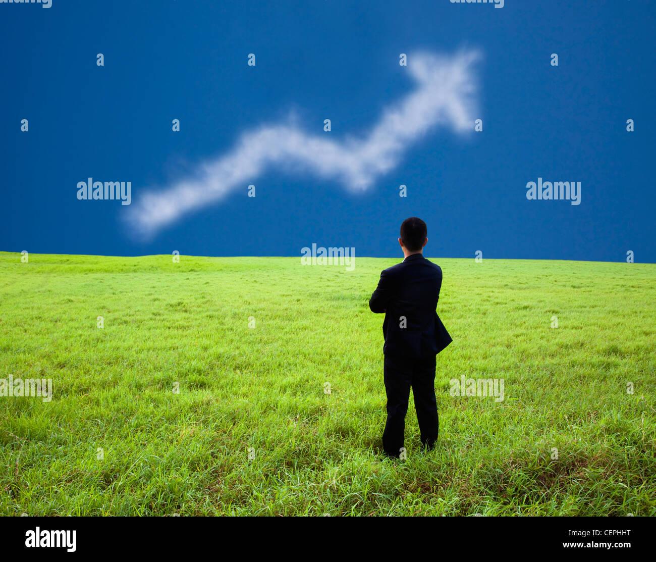 Businessman stand dans la prairie et de regarder le résultat de l'entreprise graphique cloud Photo Stock