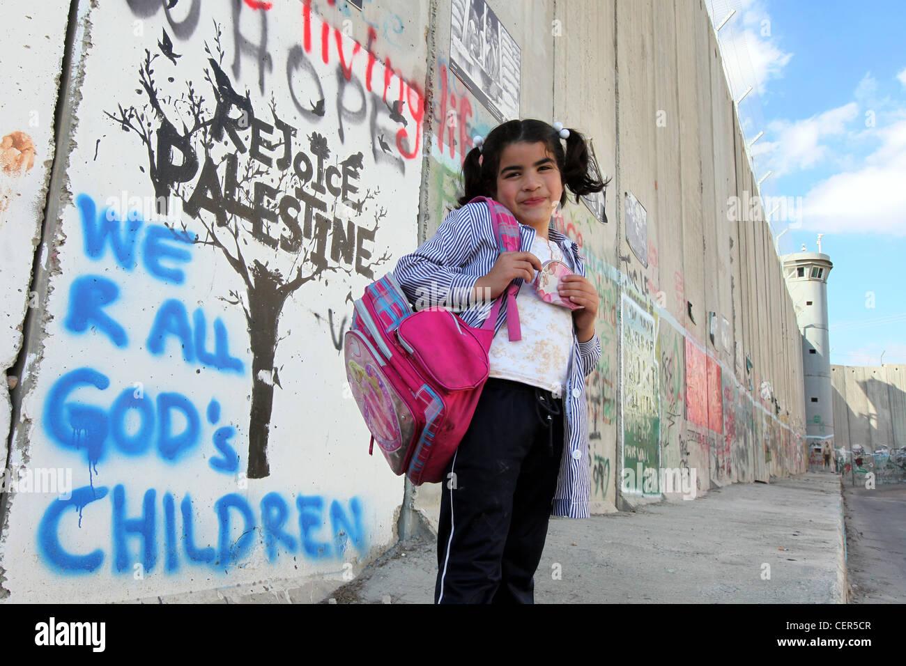 Fille debout au mur de séparation israélien. Ce mur sépare les terres palestiniennes en Cisjordanie Photo Stock