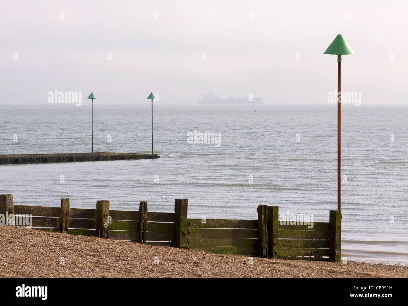 Épi en bois sur la plage à Leigh-on-Sea avec un navire à l'horizon. Photo Stock