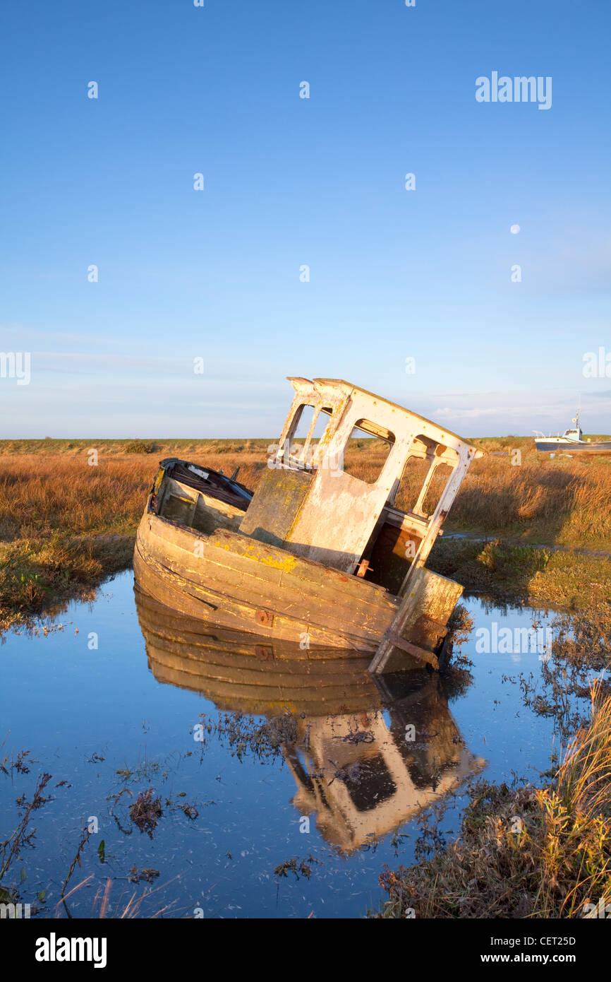 Un bateau abandonné à Thornham Harbour à la première lumière. Photo Stock