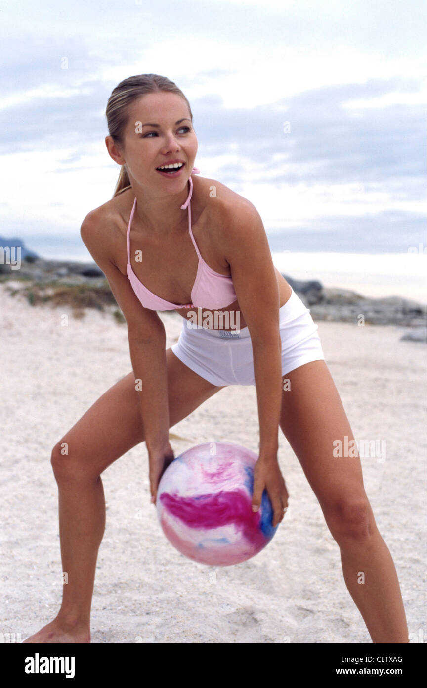 Femme blonde debout jambes écartées et les genoux pliés sur une plage de sable blanc, tenant un ballon Photo Stock