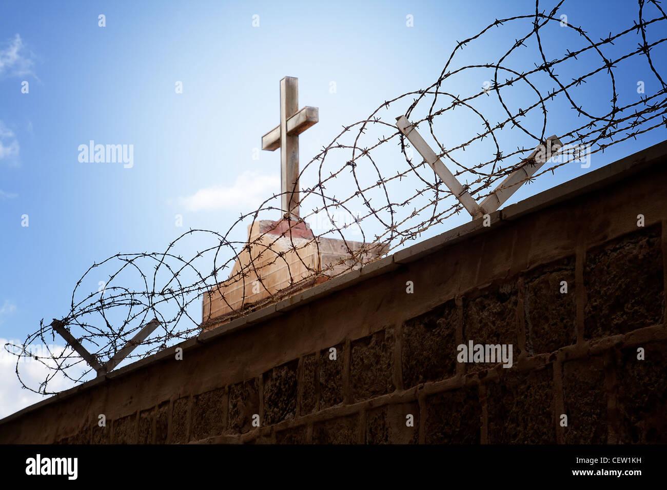 La guerre et la religion concept - Croix-Rouge et du fil de fer barbelé sur ciel bleu Photo Stock