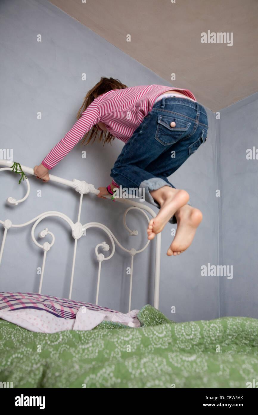 Sept ans girl holding cadre de lit et de sauter haut au-dessus de son lit. Photo Stock