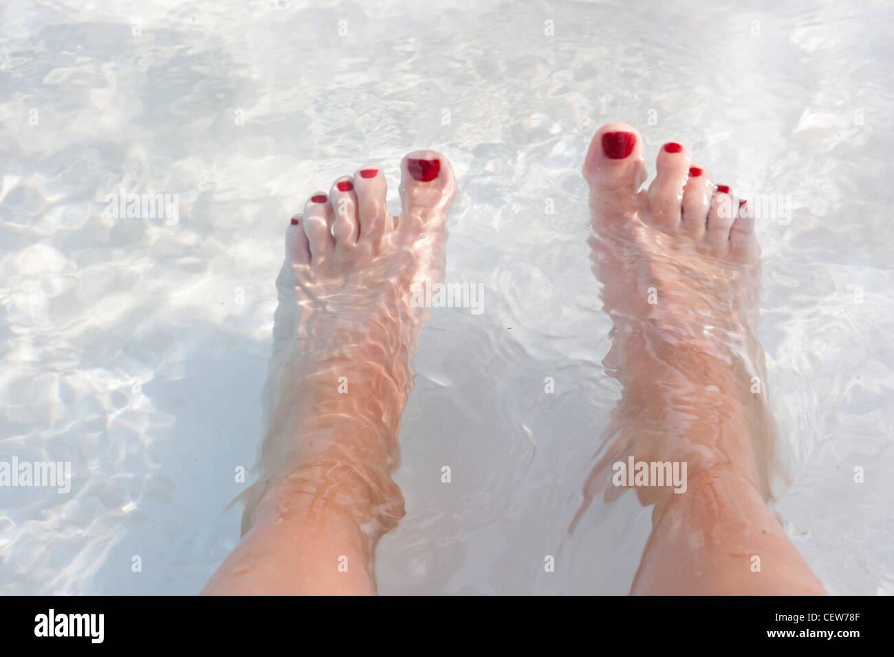 Pieds dans l'eau avec l'ongle rouge polish Photo Stock