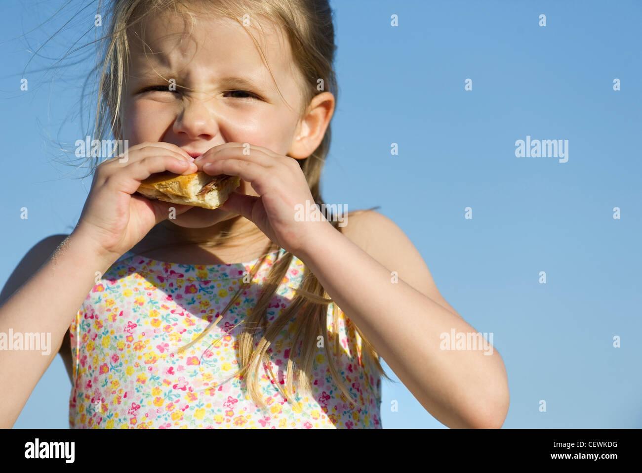 Girl eating sandwich en plein air Photo Stock
