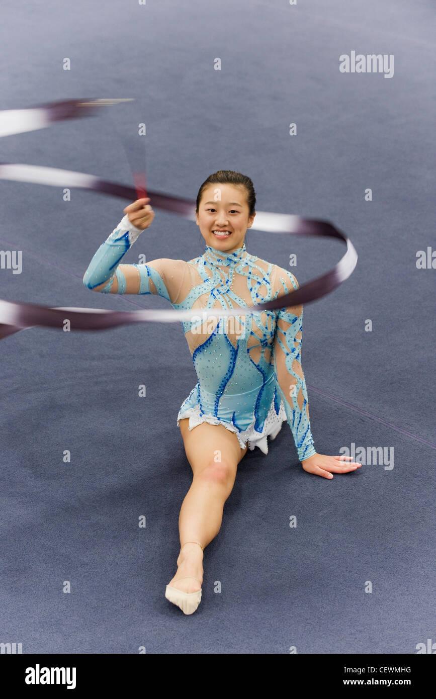 Femme gymnast étage avec ruban de routine Photo Stock