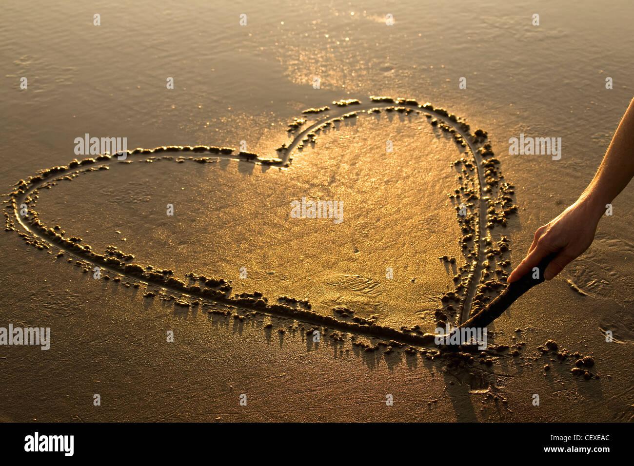 Forme de coeur gravé dans le sable d'une plage au coucher du soleil avec une main tenant un bâton; Photo Stock