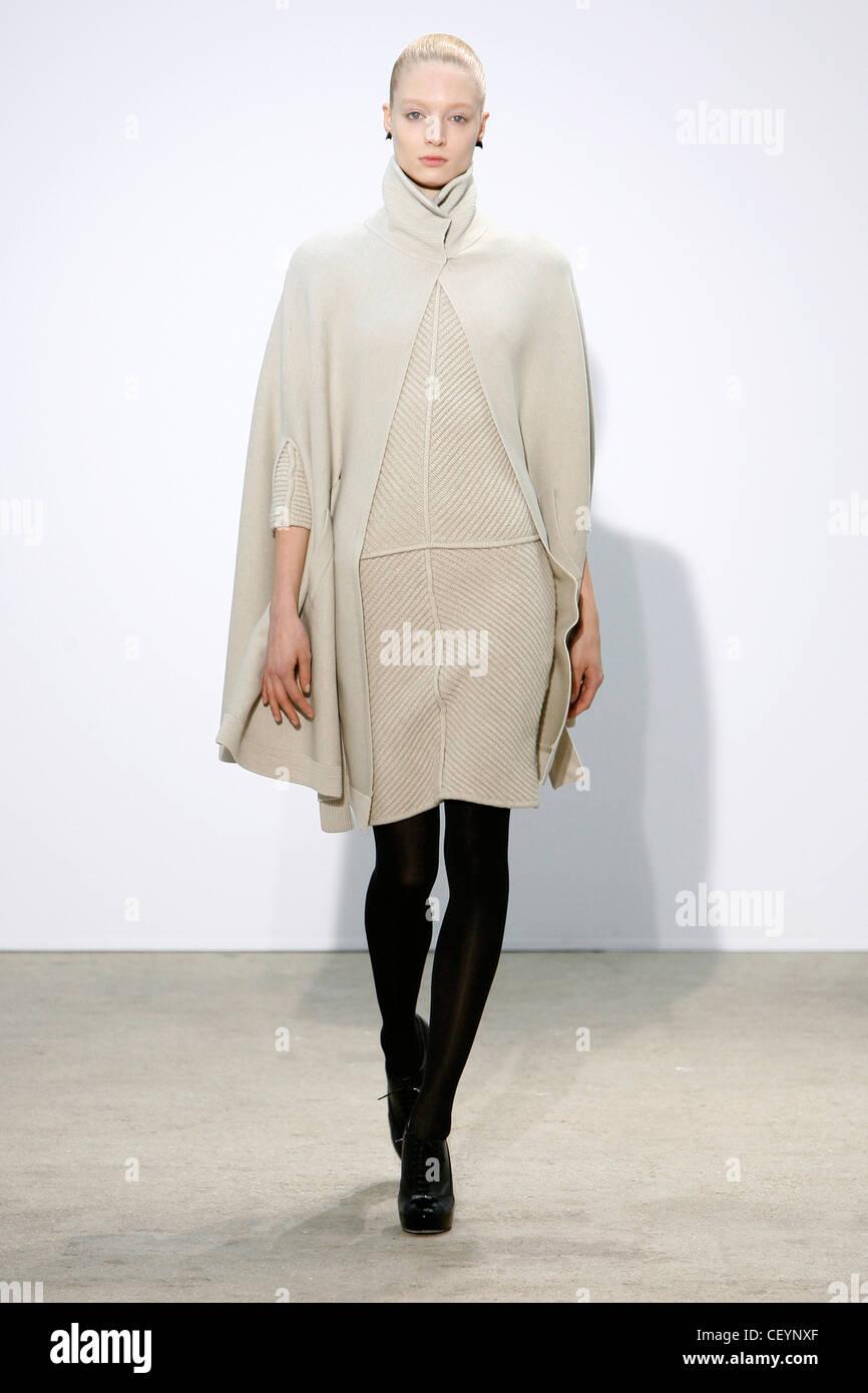 22baa865e62e Thierry Mugler Paris Prêt à Porter Automne Hiver manteau blanc manteau sur  robe blanche striée, collants noirs et bottes chaussures noir