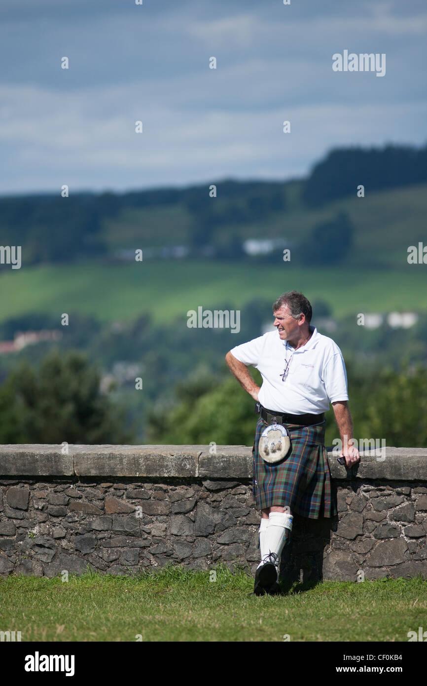 Un homme dans un kilt traditionnel et sporren est à côté d'un mur dans le château de Stirling Photo Stock