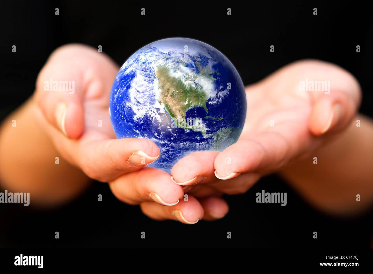 Les mains soigneusement holding Earth planet. Monde de verre Photo Stock