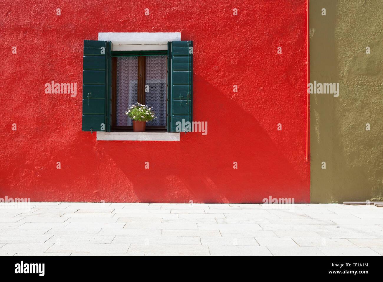 Un Pot de Fleurs se trouve dans une fenêtre avec des volets ouverts dans bâtiment peint en rouge vif; Photo Stock