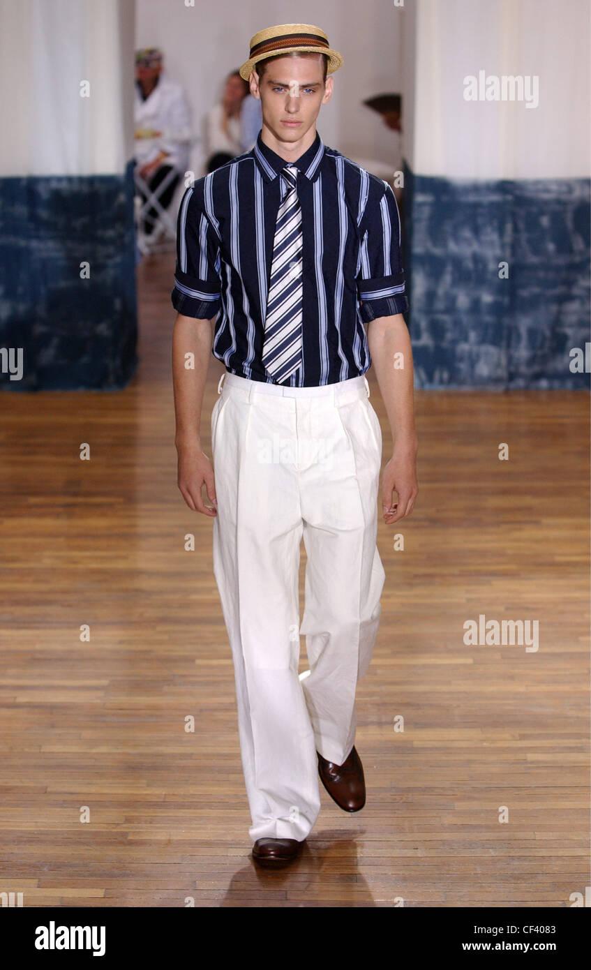 ef5cea4c3670 Kenzo Homme Paris S S modèle masculin de porter chemise et cravate rayée  bleue avec un pantalon blanc, et chapeau brun