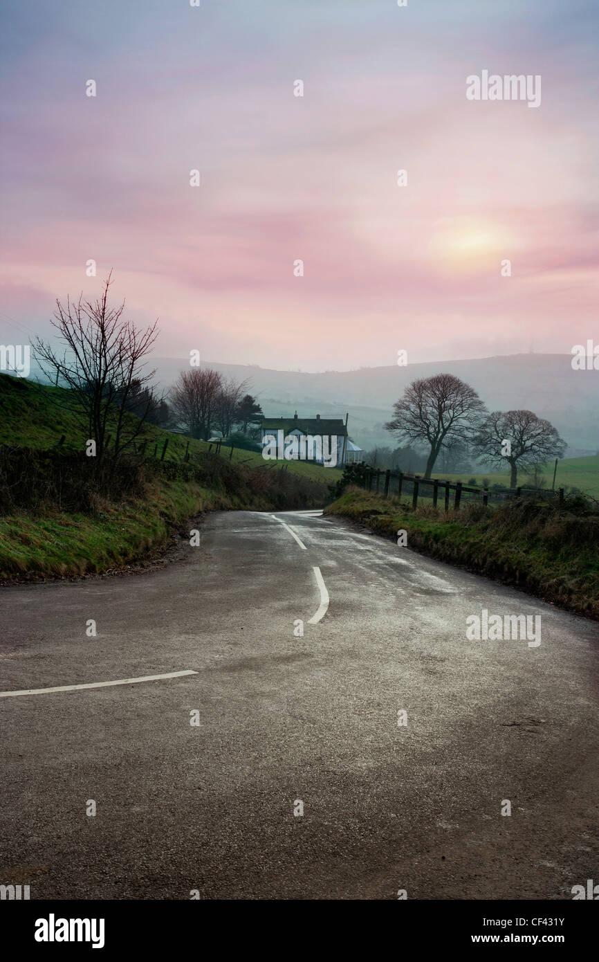 Une route de campagne qui traverse le coeur de la campagne de Cheshire sur un jour d'hiver brumeux. Photo Stock