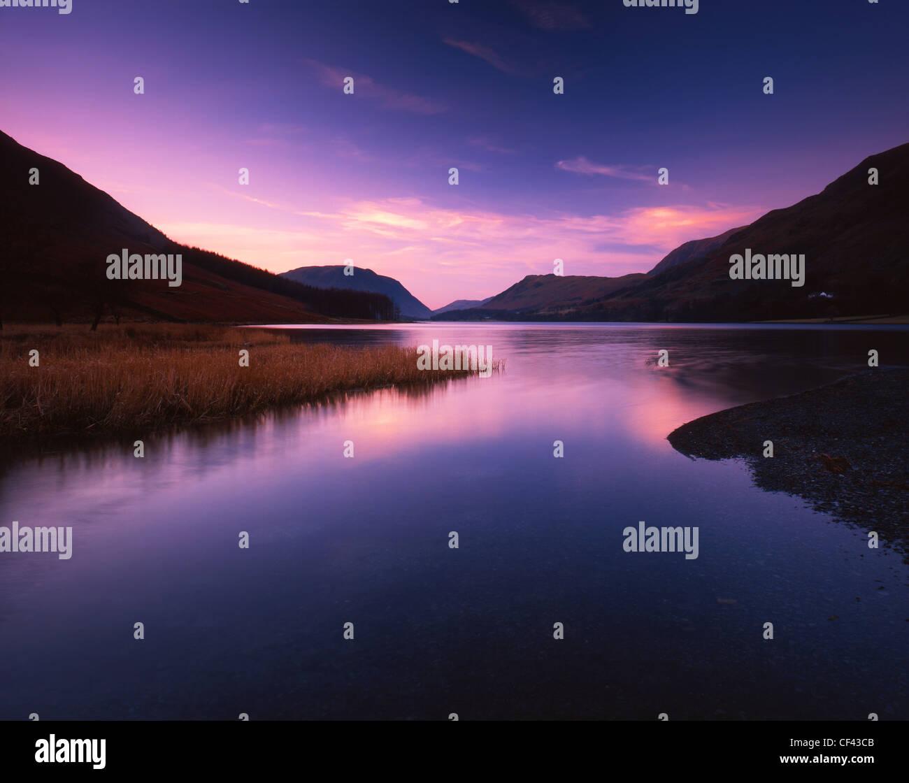 La recherche à travers les eaux calmes de la lande dans le district du lac au coucher du soleil. Photo Stock
