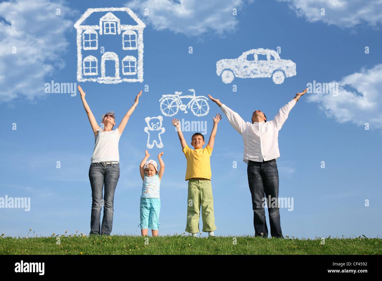 Famille de quatre sur l'herbe avec les mains en l'air et rêve Photo Stock