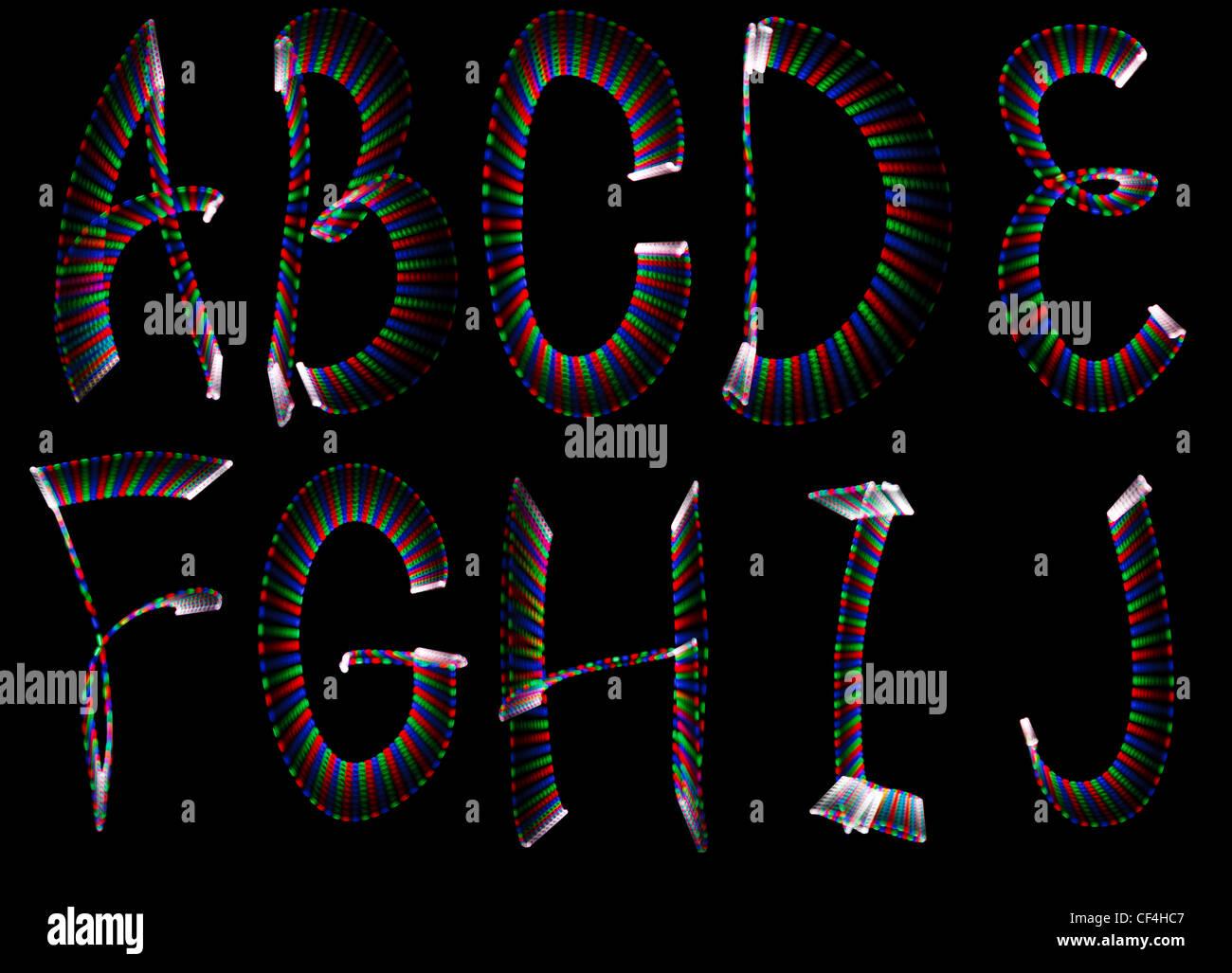 Lettres arc-en-ciel lumineux, une partie de l'alphabet sur fond noir. Isolées. Photo Stock