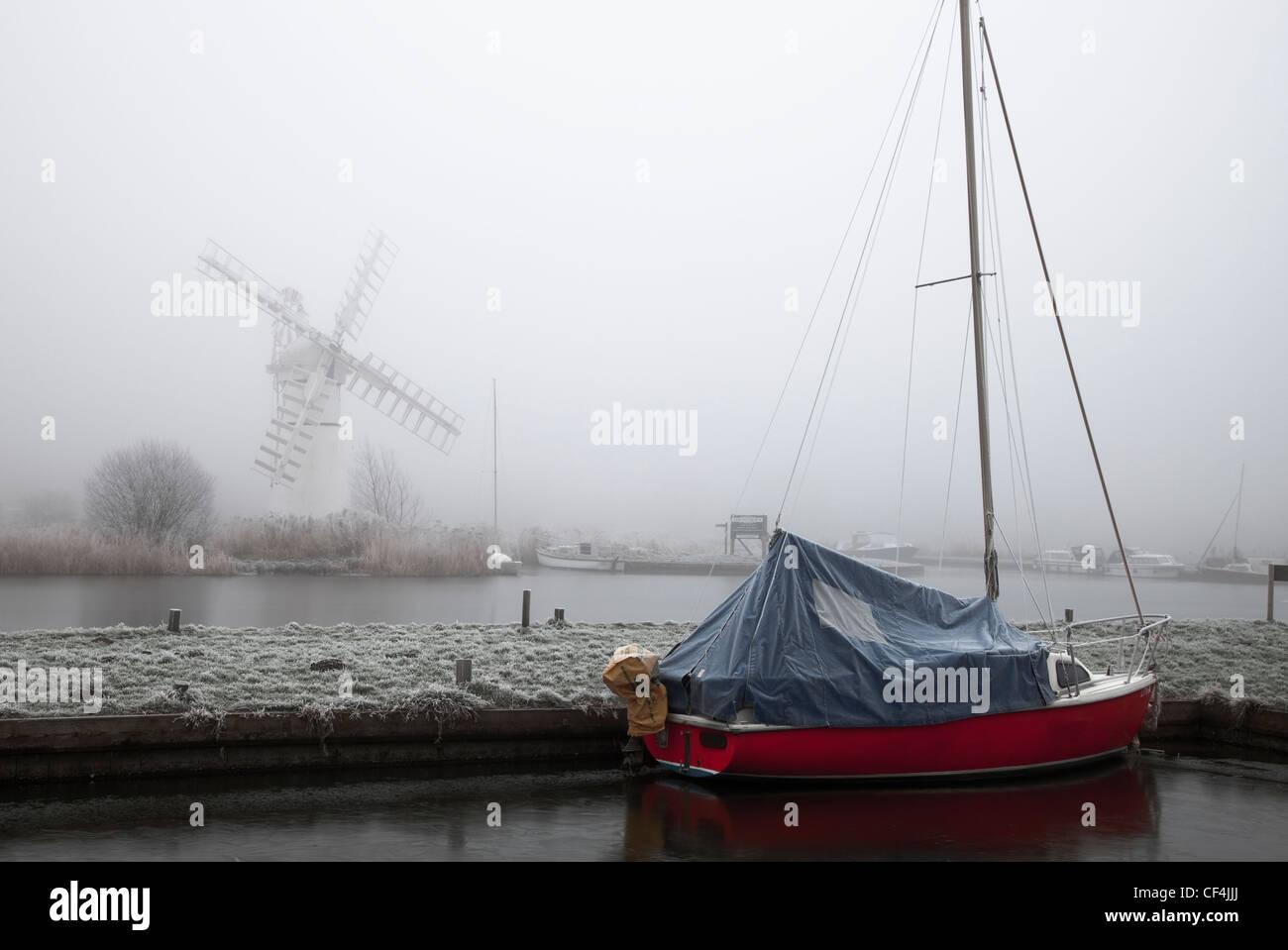 Thurne Moulin se dresse dans la brume tandis qu'un voile rouge est amarré dans l'avant-plan, à Norfolk. Banque D'Images