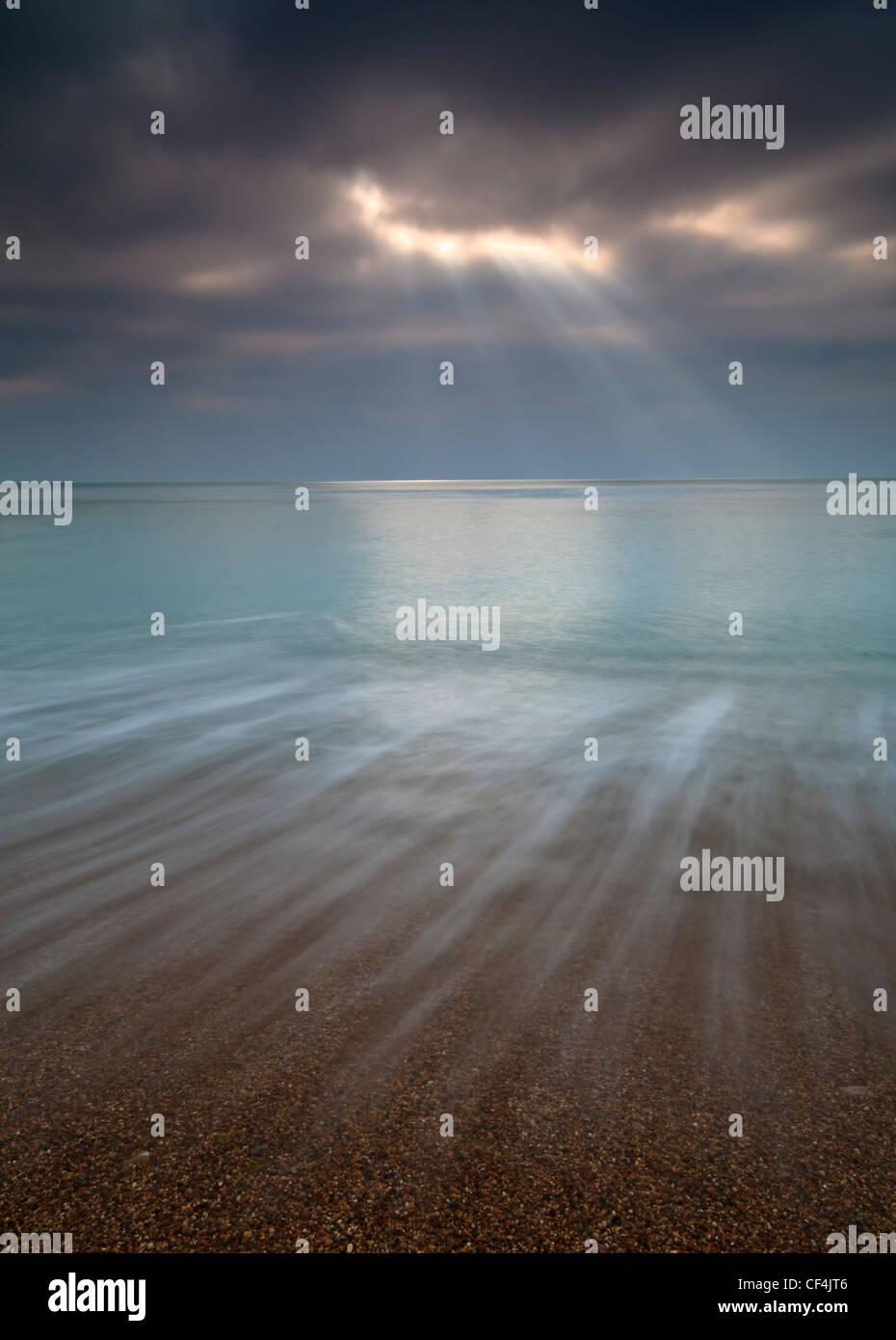 Rayons crépusculaires sur la mer à Burton Bradstock. Photo Stock