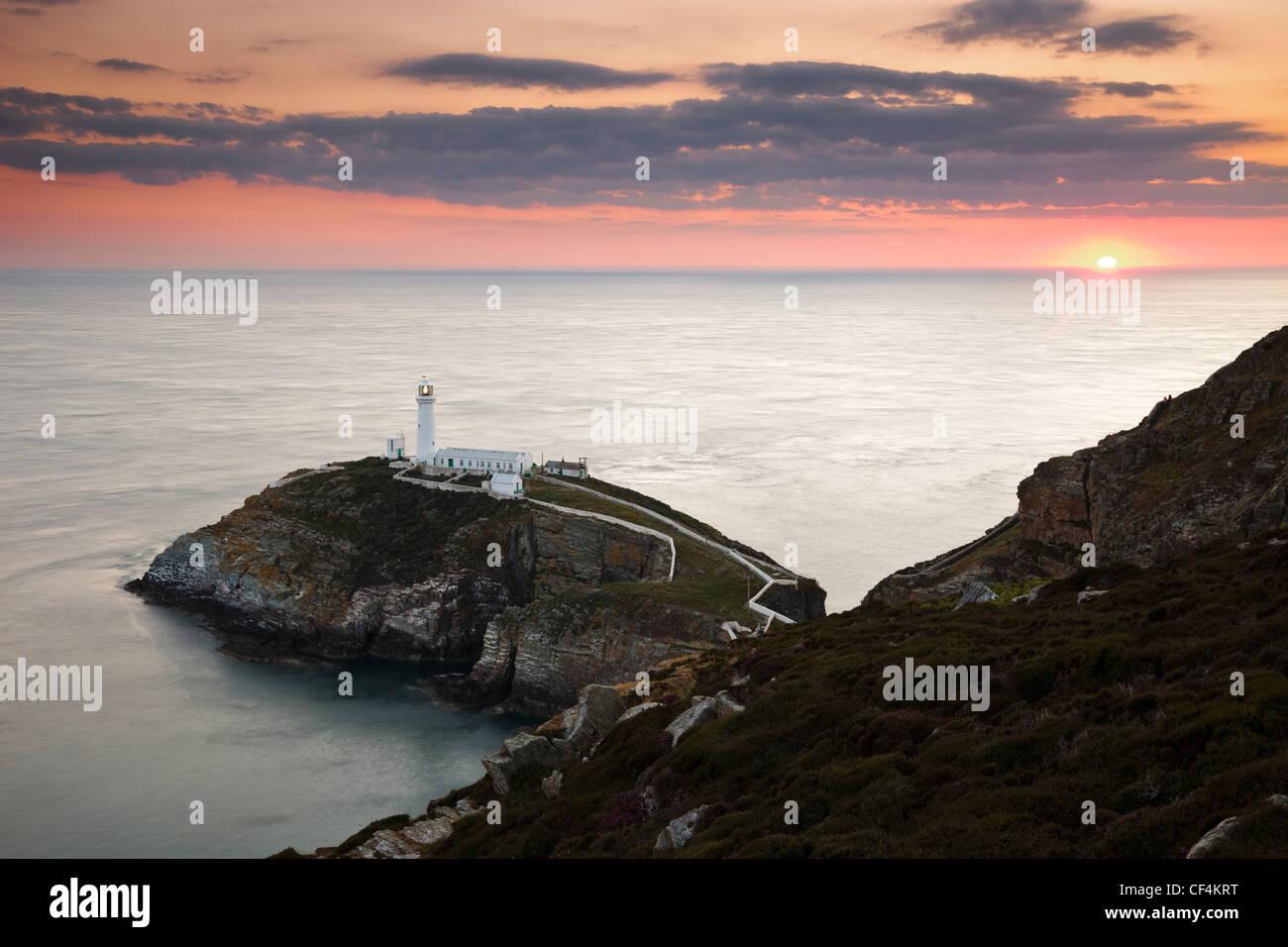 Le coucher de soleil sur l'horizon derrière phare de South Stack, un phare spectaculaire juste à côté Photo Stock