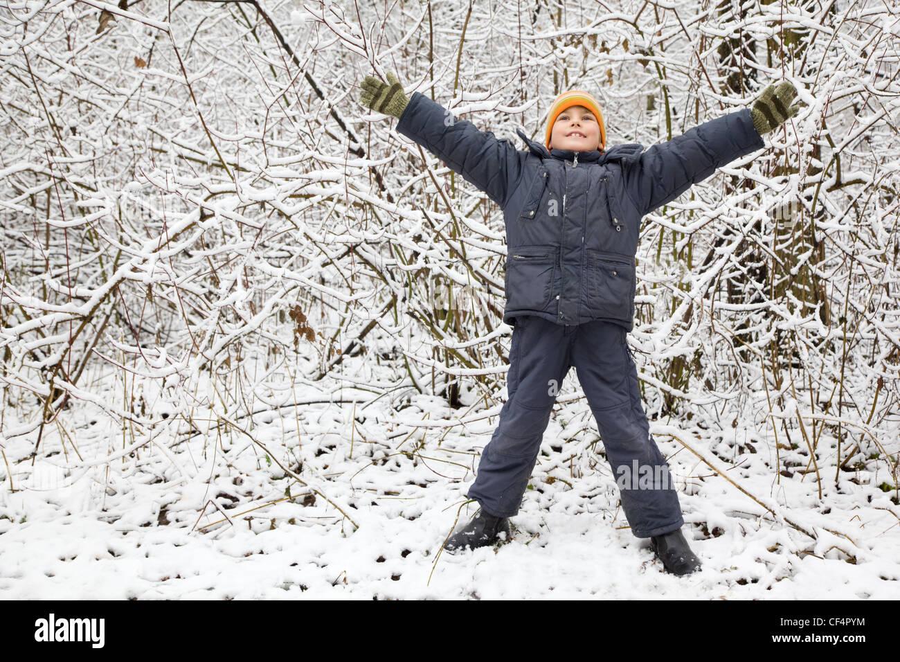 Boy a levé les mains vers le haut dans le bois en hiver Photo Stock