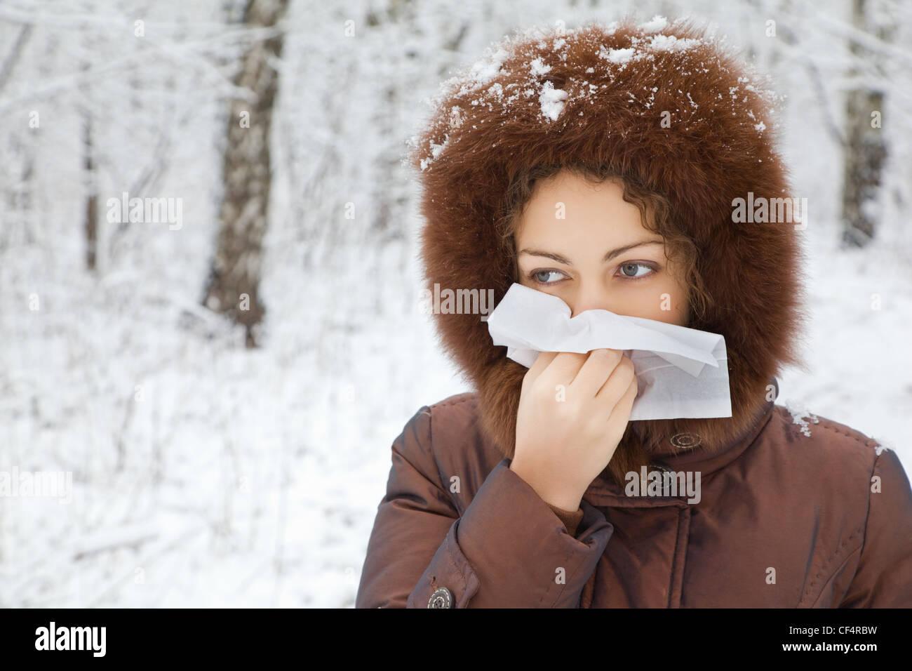 Jeune femme avec foulard blowing nose dans le bois en hiver Photo Stock