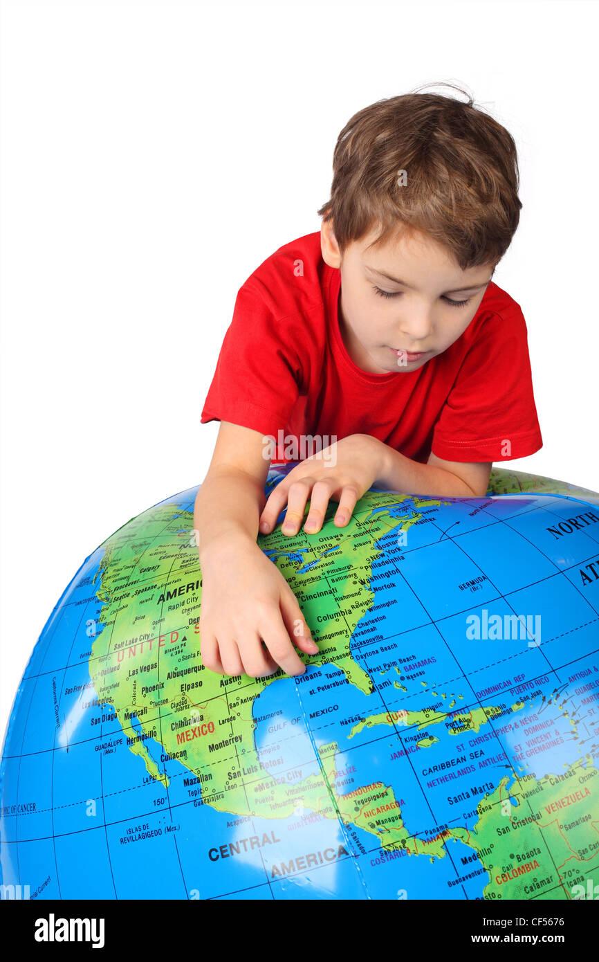 Garçon en chemise rouge s'appuie sur inflatable globe isolé sur fond blanc Photo Stock