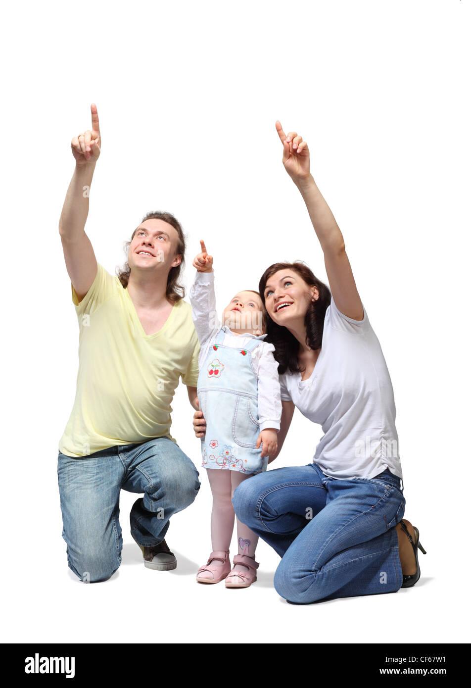 Heureuse mère, père et fille s'asseoir et de pointer du doigt vers le haut Photo Stock