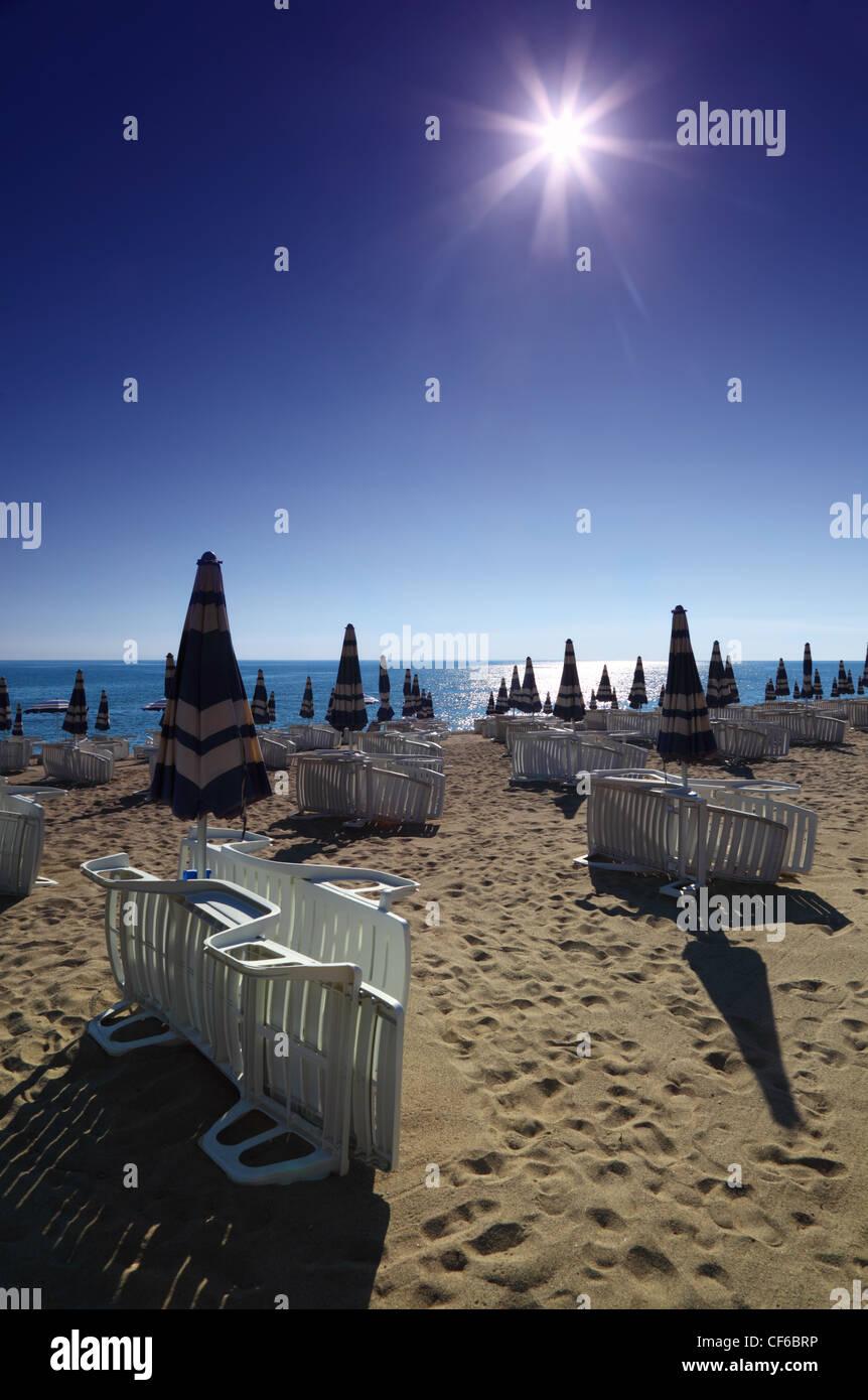 Plage de sable vide pliée avec parasols et chaises longues, soleil et ciel sans nuages Photo Stock