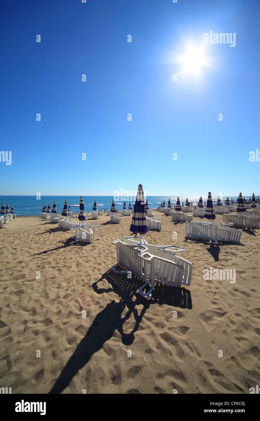 Plage de sable vide et ouverte avec parasols et chaises longues, soleil et ciel sans nuages Photo Stock