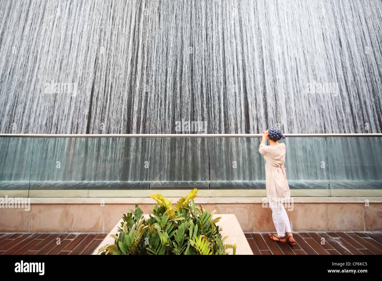 Jeune beauté femme en chemise blanche, debout près de grande fontaine, un corps entier Banque D'Images
