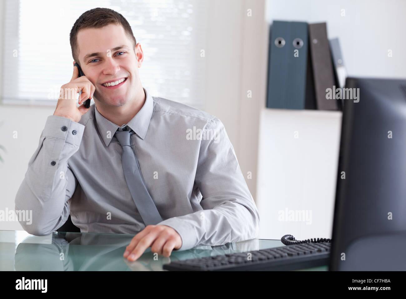 Businessman getting pleasant news sur la téléphonie mobile Photo Stock