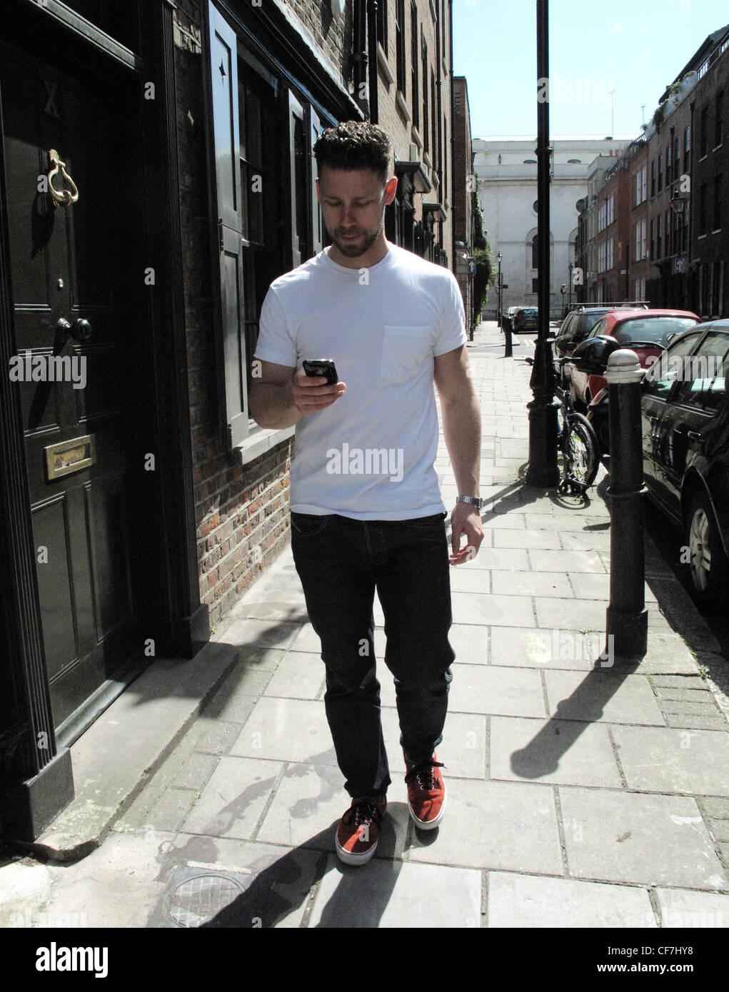 e23cd74098c9 homme-avec-les-cheveux-court-brunette-portant-un-t-shirt-blanc-jean-noir-et-rouge-des-formateurs-marchant-dans-la-rue-a-laide-dun-i-phone-cf7hy8.jpg