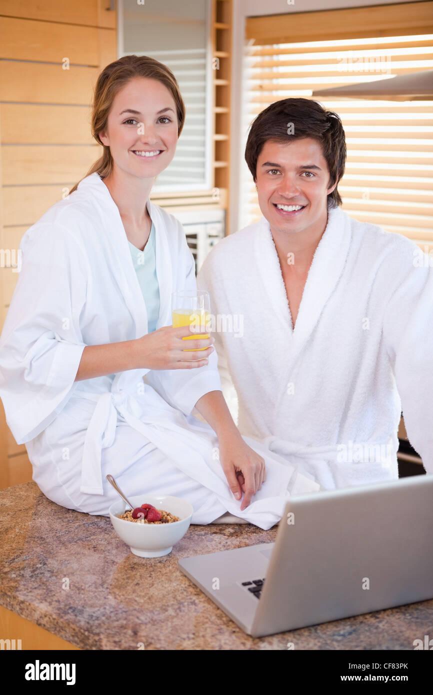 Portrait d'un couple charmant de prendre le petit déjeuner tout en utilisant un ordinateur portable Photo Stock