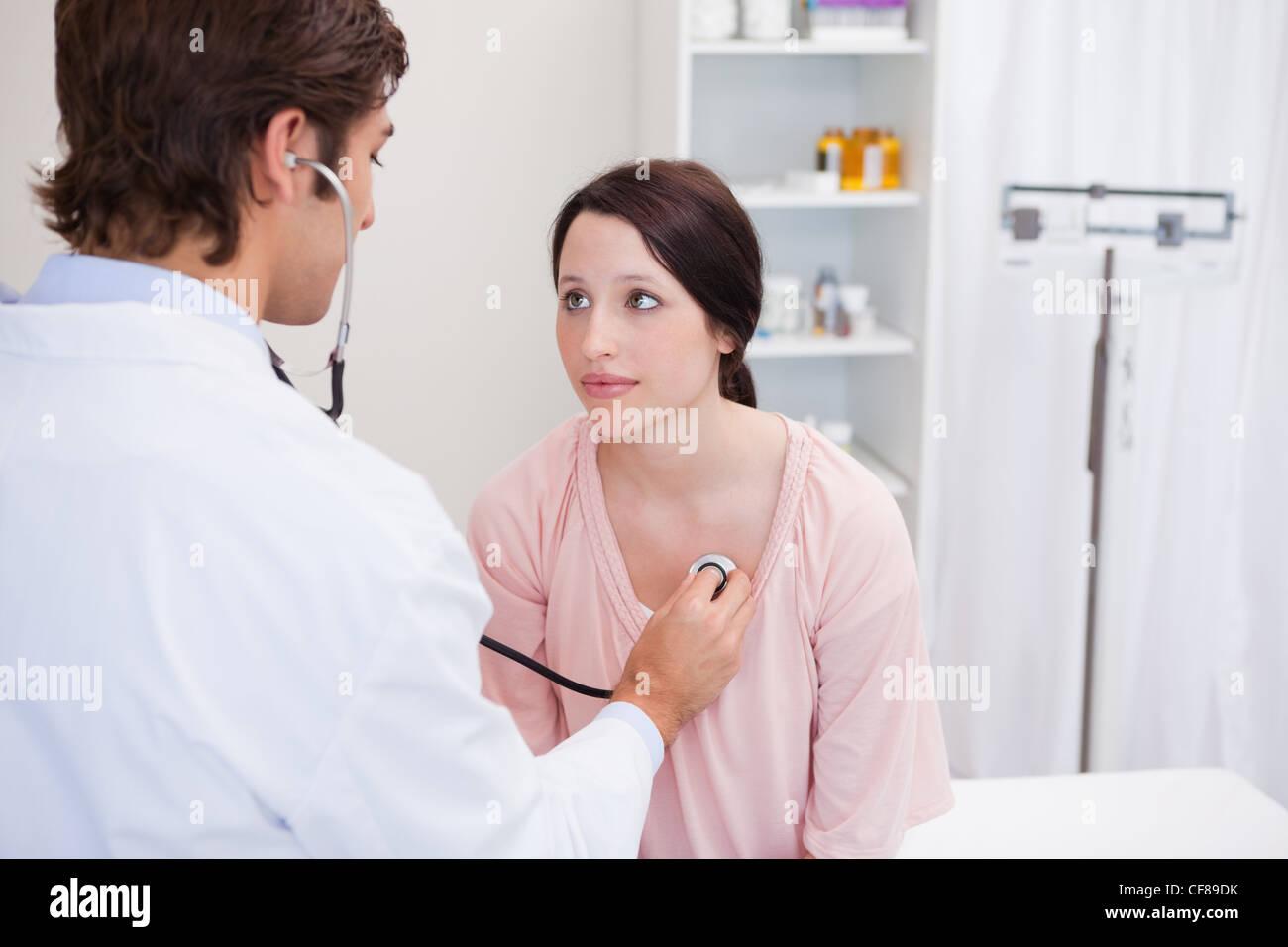 Jeune médecin de prendre son rythme cardiaque des patients Photo Stock