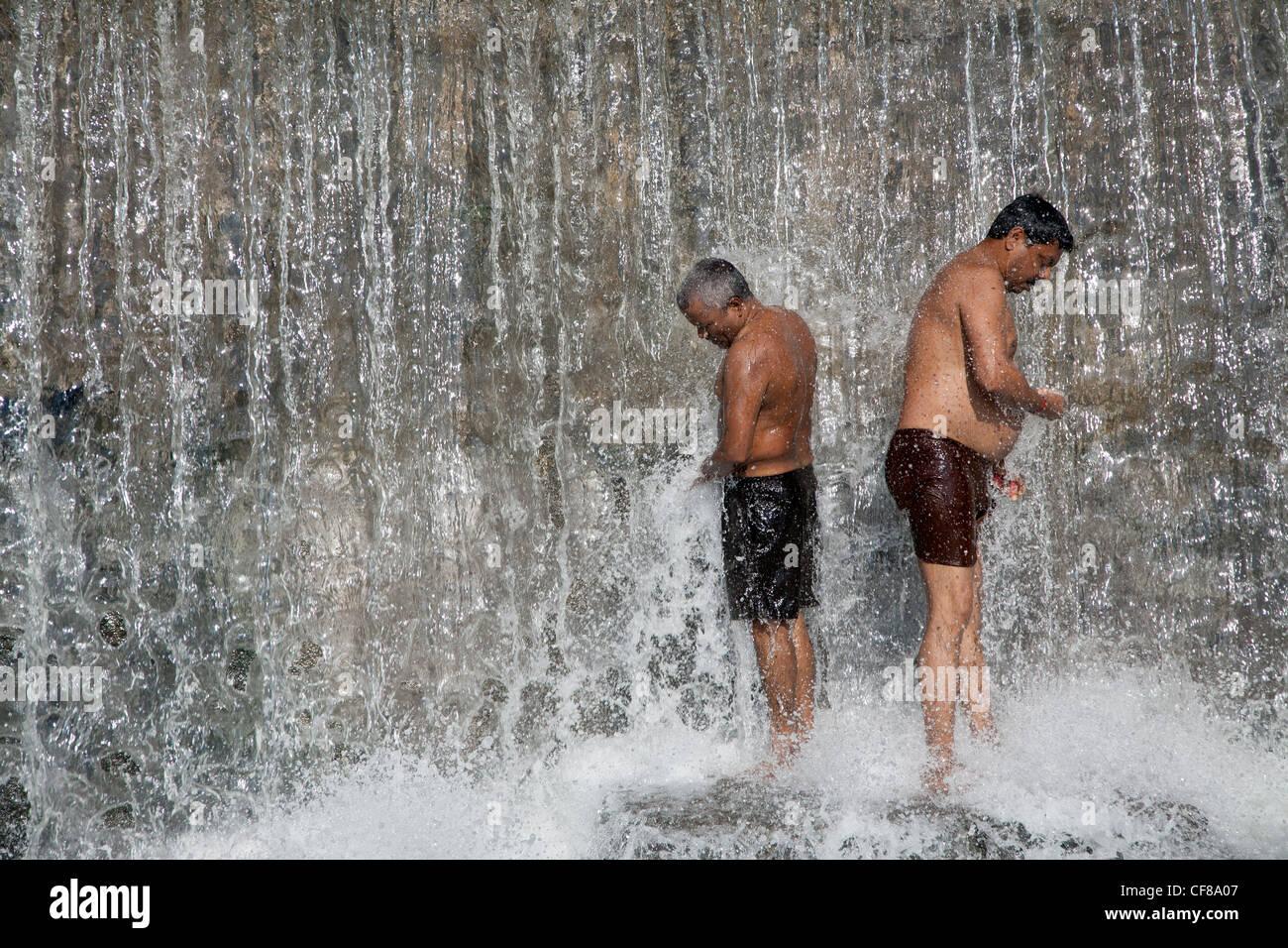 Laver les hommes sous une cascade. La rivière Godavari. Nasik. L'Inde Photo Stock