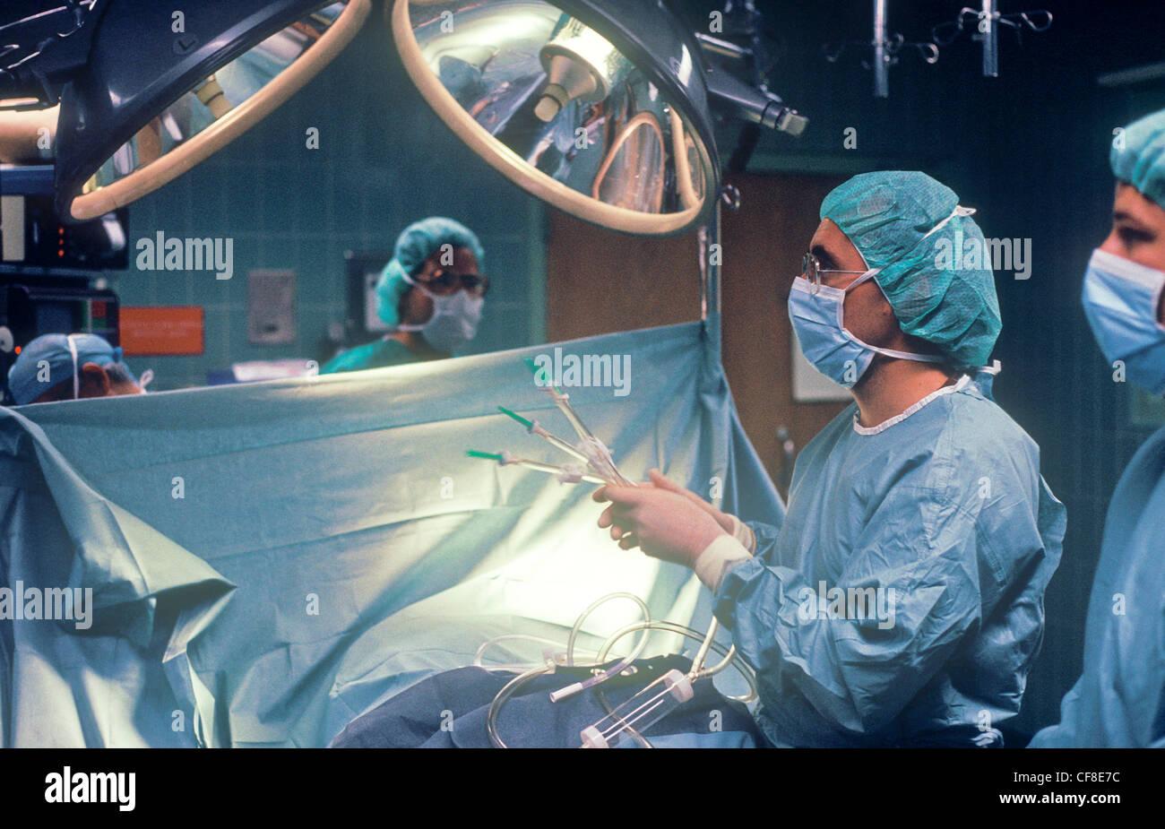 Un chirurgien d'effectuer la chirurgie sur un patient dans la salle d'opération. Photo Stock