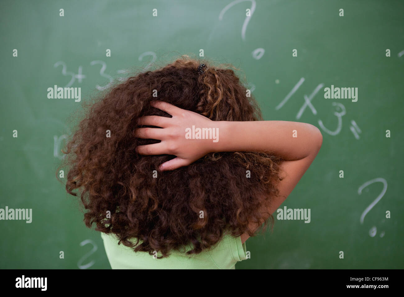 Lycéenne de penser à tout en algèbre de rayer l'arrière de sa tête Photo Stock