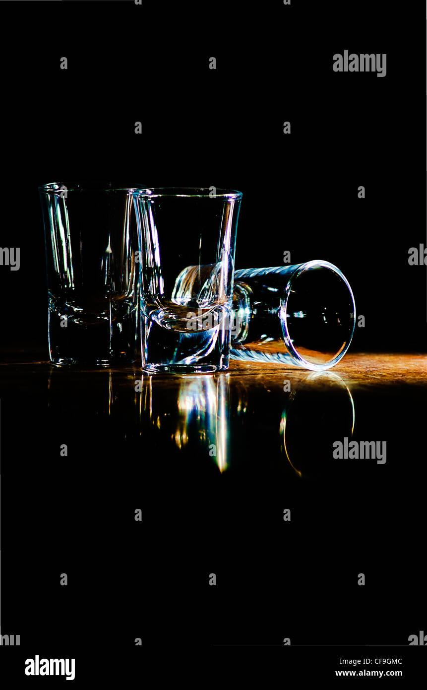 Trois verres sur le bar dans un rayon de lumière Photo Stock