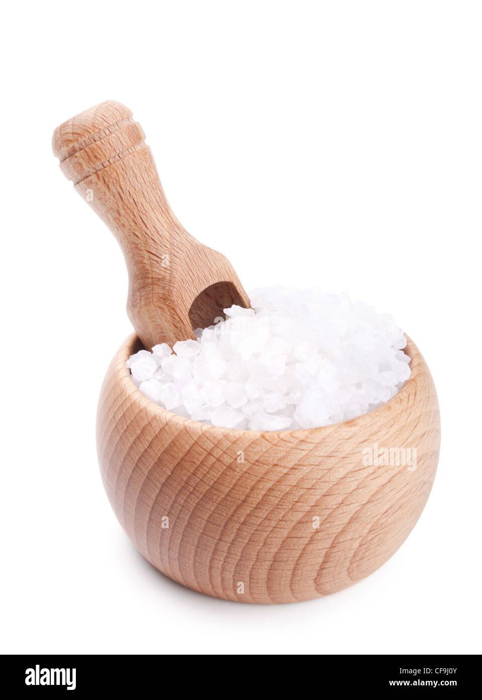 Scoop en bois dans un bol rempli de sel de mer isolé sur fond blanc Photo Stock