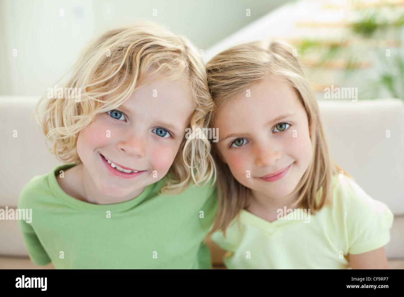 Frères et sœurs sourire sur le canapé Photo Stock