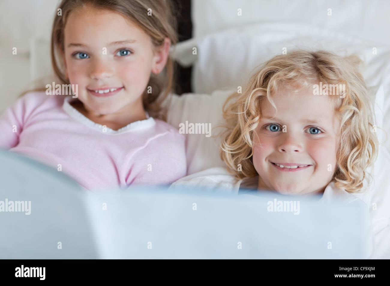 Frères et sœurs lecture histoire de temps de lit Photo Stock