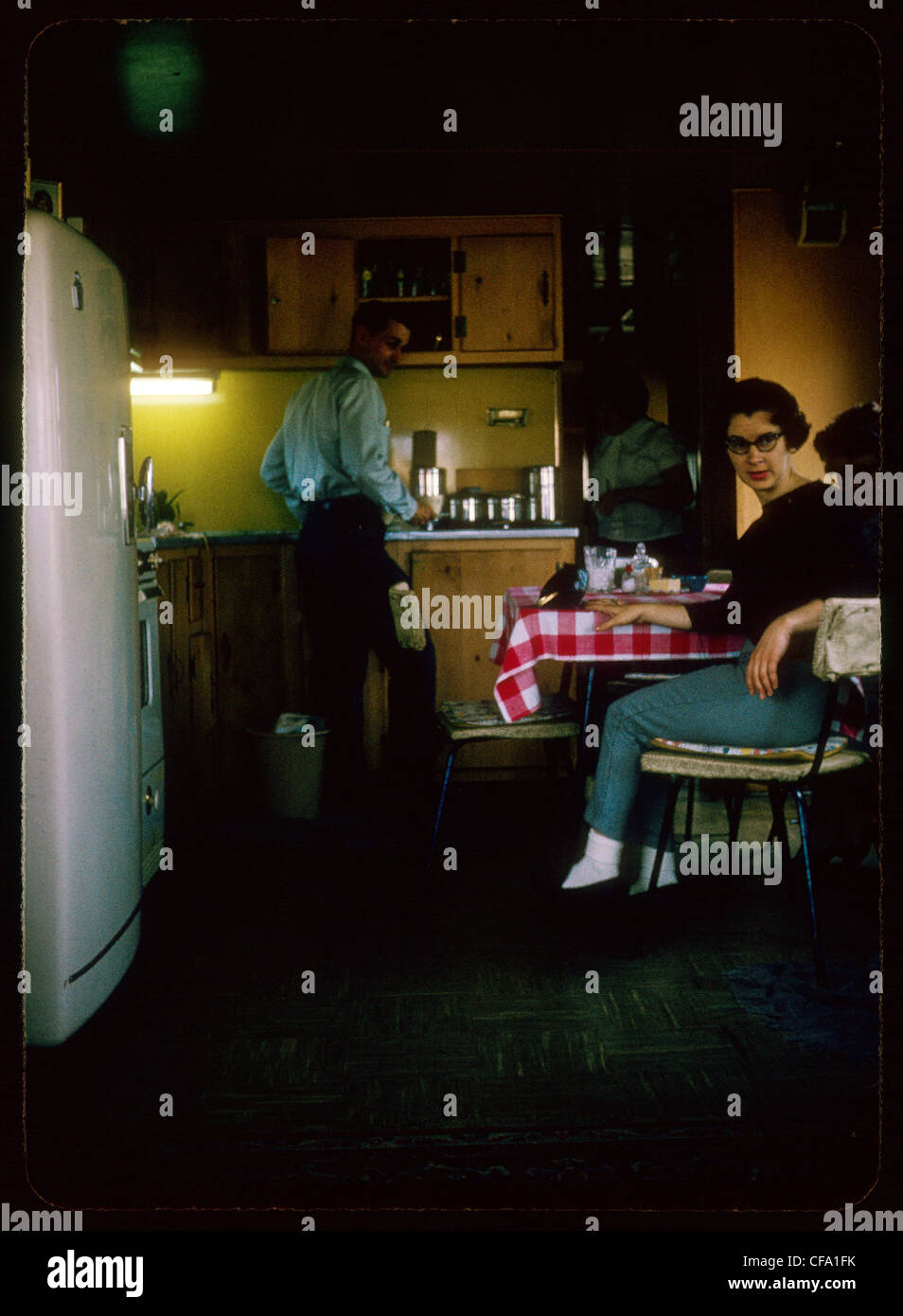 Femme assise homme debout dans la cuisine pendant les années 1960 Photo Stock