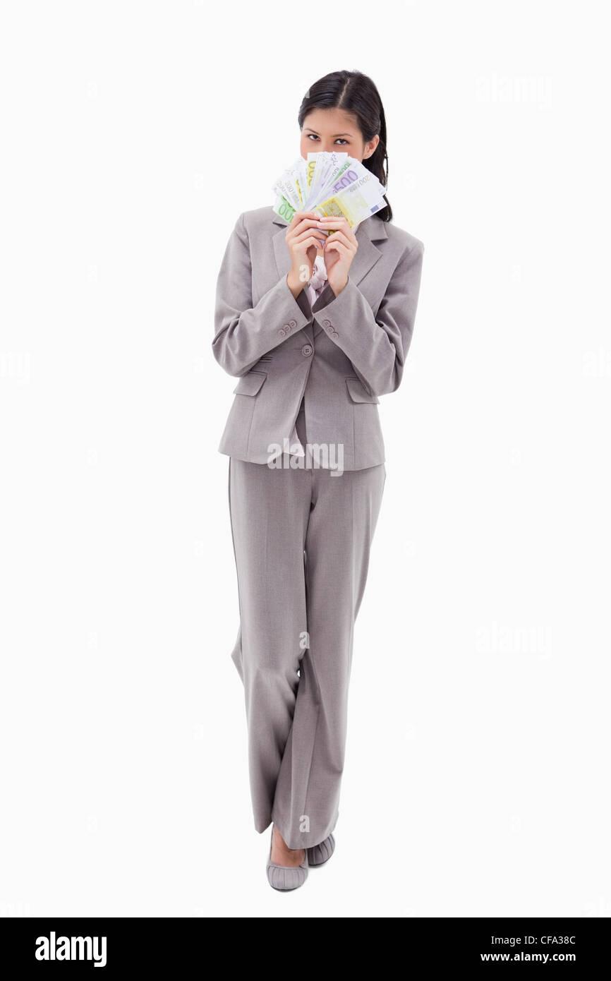 Businesswoman se cachant derrière des billets de banque Banque D'Images