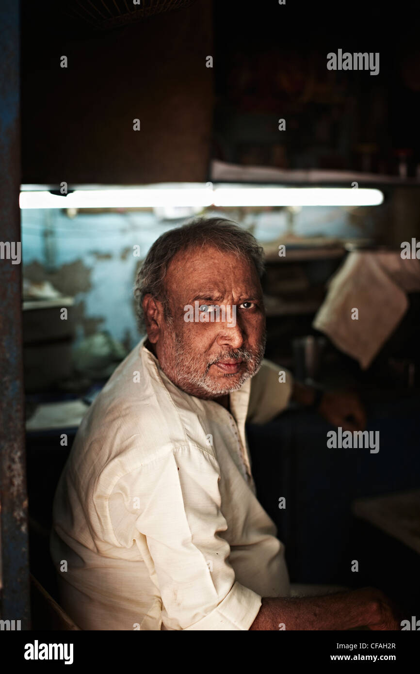 Middle-aged man sitting in shop Photo Stock
