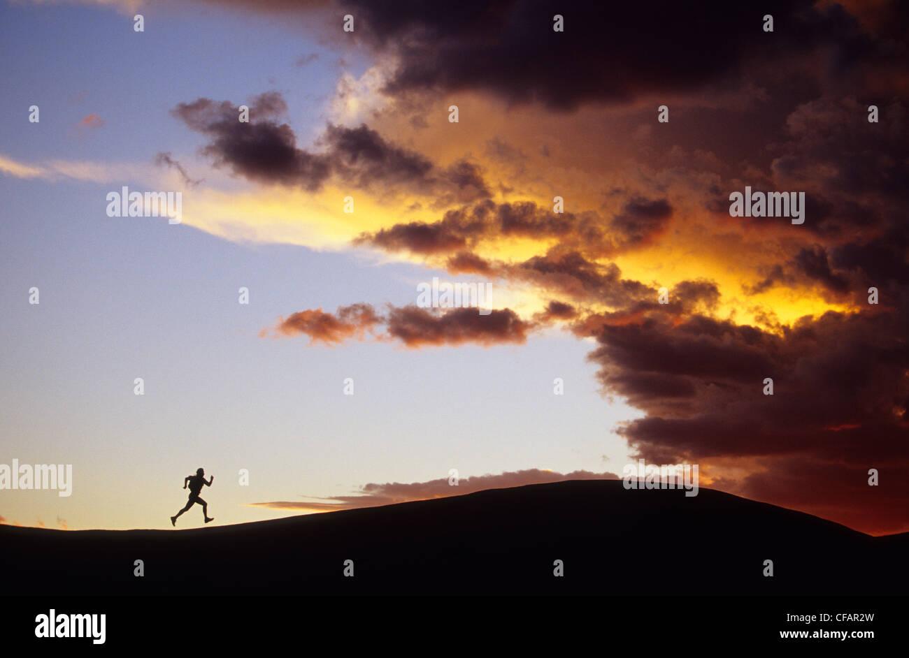 Silhouette femme exécutant ridge distance vers Photo Stock