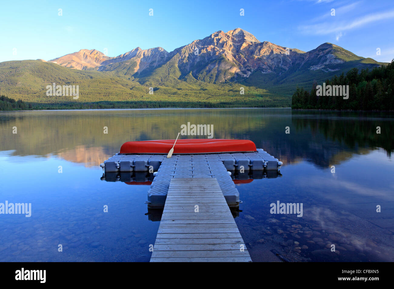 Red canoe sur dock à Pyramid Lake avec Pyramid Mountain, Jasper National Park, Alberta, Canada. Banque D'Images