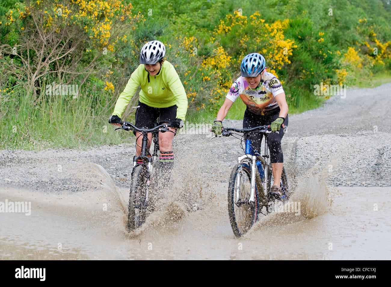 Deux femmes adultes rire cycliste flaque près de Photo Stock