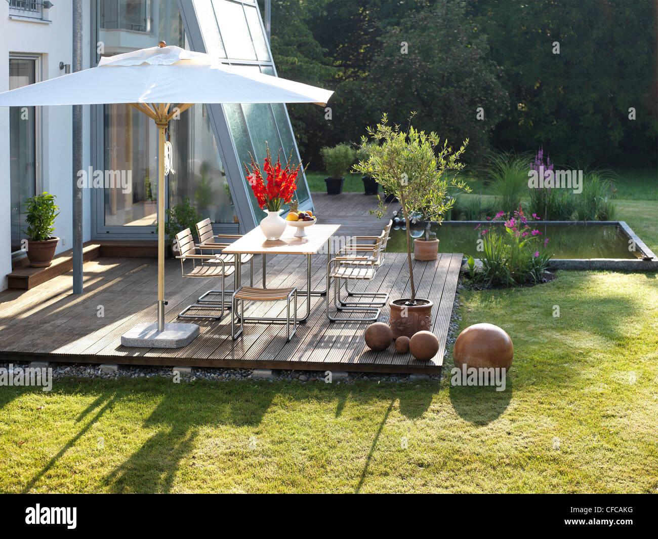 Maison moderne avec terrasse et meubles de jardin, étang ...